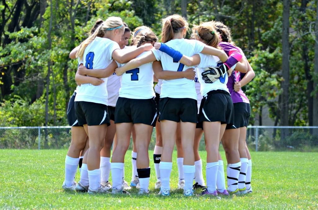 Members of the girls' soccer team huddle up at their charity game to benefit Camelot for Children