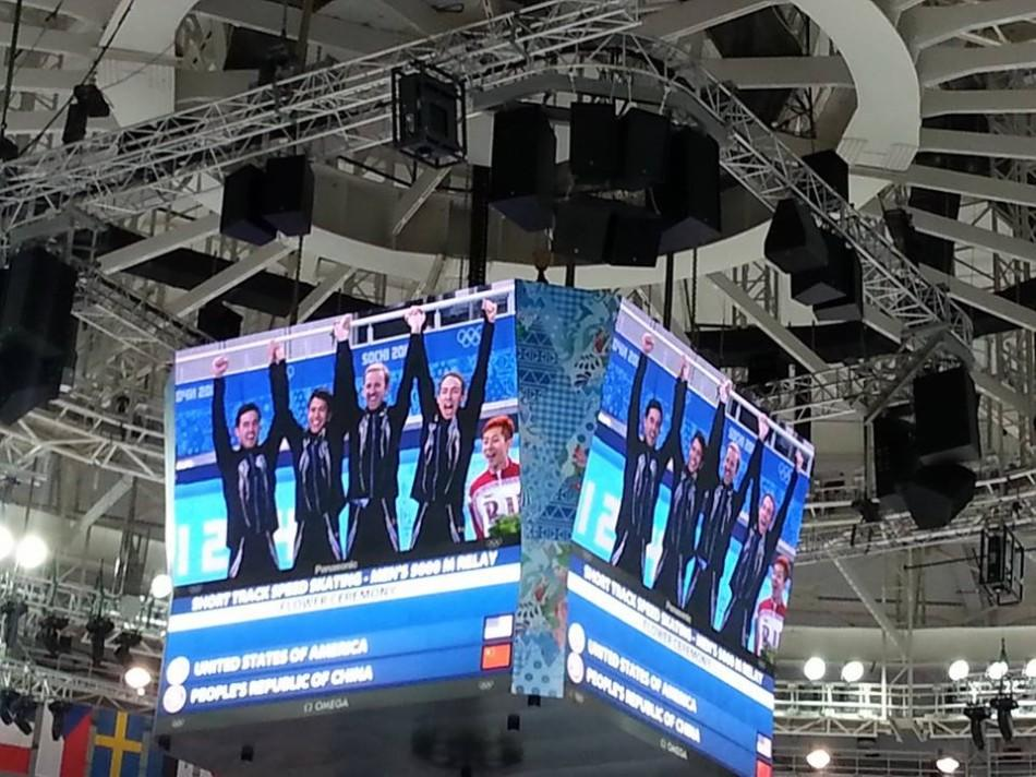 The men's short track speed skating relay team celebrates their silver medal right after the race on the jumbotron.