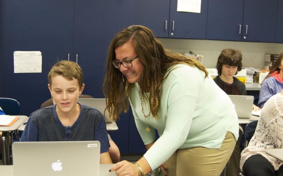 Ms. Michelle Peralta helps a student with an assignment.