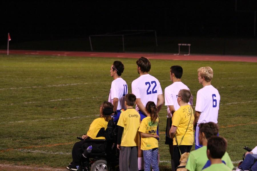 The Camelot children walked the Solehi soccer players onto the field at the start of the game.