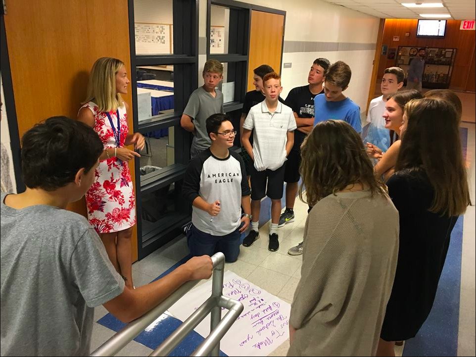 Freshmen work to generate ideas with the help of a teacher during a class assembly.