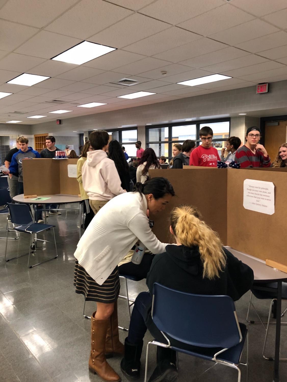 Teacher Mrs. Caryn Bronfenbrenner shows a student how to cast her ballot.