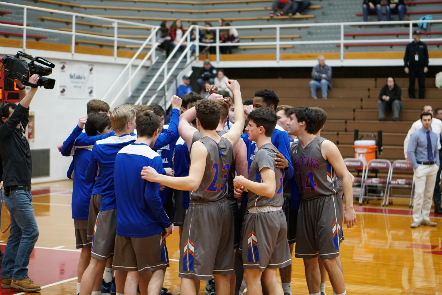 The team huddles up before a District XI playoff game in February. They would go on to win the contest 72-65 behind 26 points from Chris Andrews.