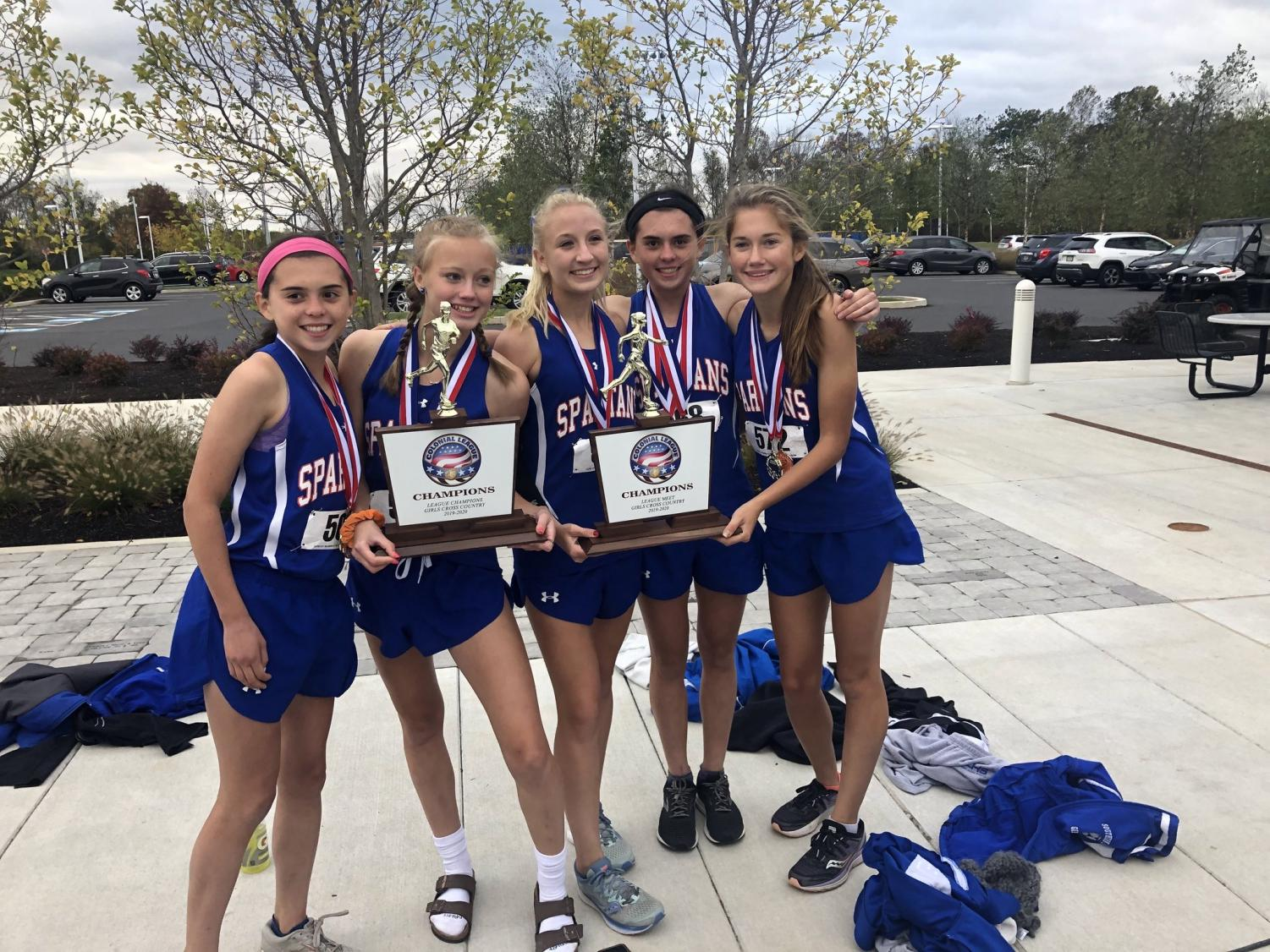 The top girls cross country runners proudly display their trophies after winning the Colonial League Championship.