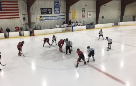 The Southern Lehigh Hockey Team in action as two players face off at the beginning of the game.