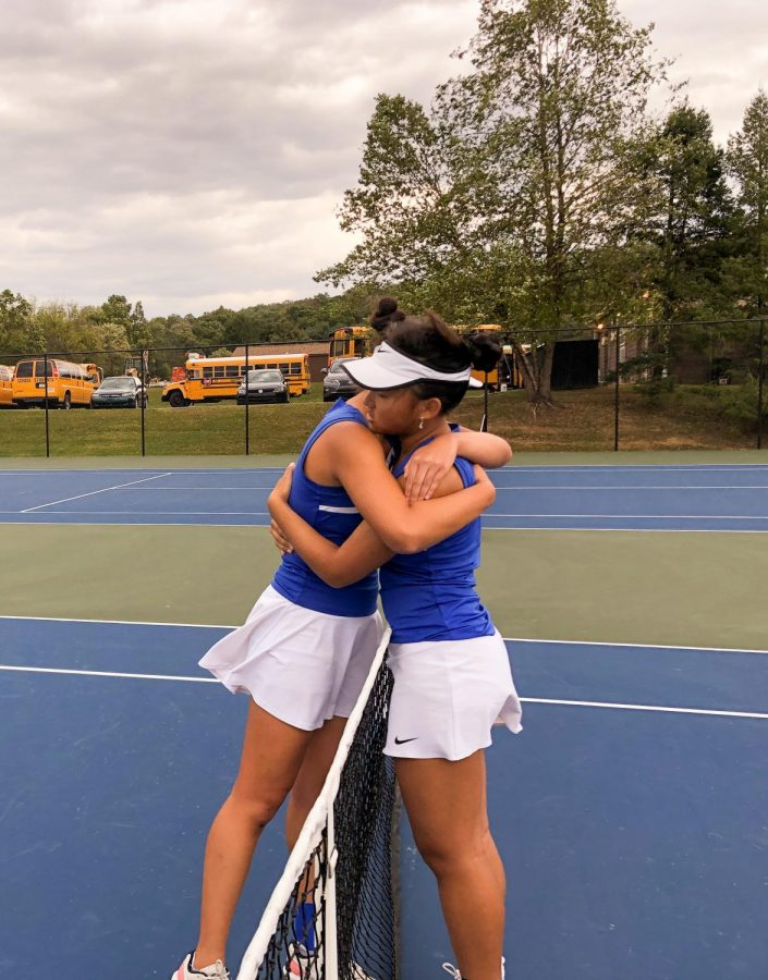 Senior Michelle Li (left) and sophomore Evelyn Wang (right) hug across the net after their District XI 3A semi-final match.